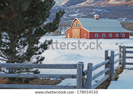 Large Red Barn in the mountains during winter at sunrise. - stock photo