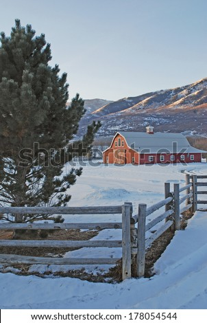 Large red barn in the mountains with a log fence during winter. - stock photo