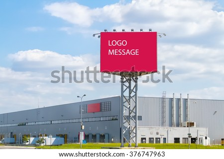 Large red billboard and Aluminum facade in front of industrial building with blue sky. Logo Message.