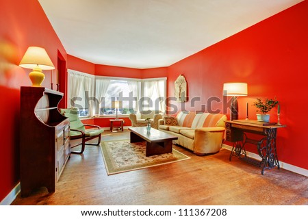 Large red living room with hardwood and antique furniture with lamps. - stock photo