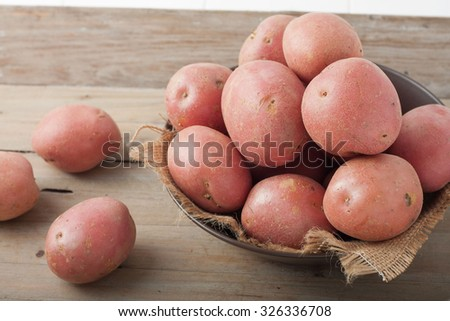 large red potatoes in a bowl on wooden background - stock photo