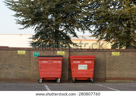 Large red Recycling Bins against a brick wall  - stock photo