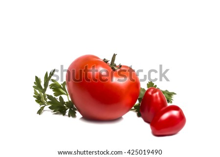 large red ripe tomato with two small and a sprig of parsley - stock photo
