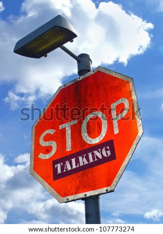 Large red road sign with the words Stop Talking. - stock photo