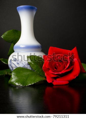 large red rose next to a white decorated vase