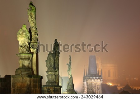 Large religious statues on the Charles bridge and distant Gothic tower in foggy night, Prague, Czech Republic - stock photo