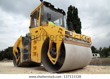 Large road-roller paving a road. Road construction - stock photo
