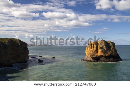 large rocky island emerging from the tropical ocean on the Great Ocean Road  - stock photo
