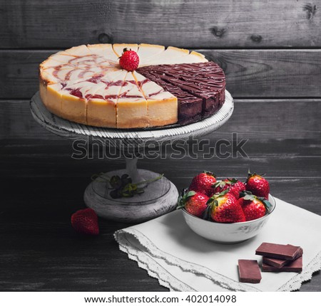 Large round assorted cheesecake, raspberry, caramel, chocolate, caramel, cut into pieces on a white pedestal, white plate with strawberry, napkin on a black wooden background - stock photo