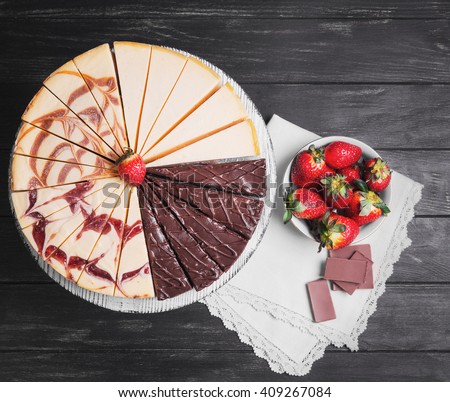 Large round assorted cheesecake, raspberry, caramel, chocolate, caramel, cut into pieces on a white pedestal, white plate with strawberry, napkin on a black wooden background, top view - stock photo
