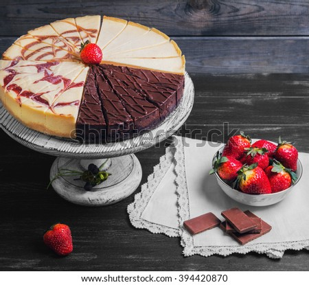 Large round assorted cheesecake torte, raspberry, caramel, chocolate, caramel, cut into pieces on a white pedestal, white plate with strawberry, napkin on a black wooden background - stock photo