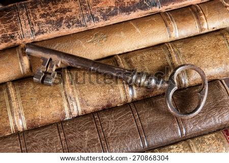 Large rusty key lying on weathered old books - stock photo