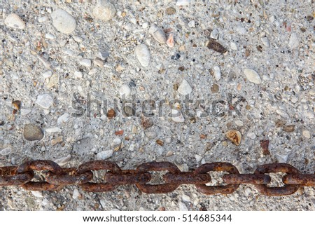 large rusty metal chain on stone wall background