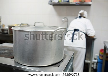 Large saucepan on the stove in the culinary workshop - stock photo