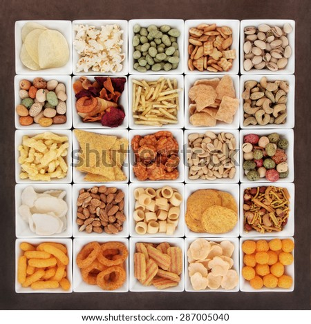 Large savory snack food selection in square porcelain bowls. - stock photo