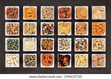 Large savoury snack food selection in square porcelain bowls. - stock photo