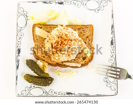 Large scoop of tuna salad sprinkled with paprika on whole grain toast with sweet gherkin in high contrast black and white setting. - stock photo