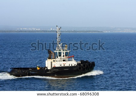 Large sea tug boat under power at sea.