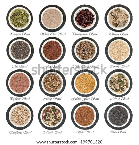 Large seed super food selection in  porcelain bowls over slate rounds and white isolated background with titles. - stock photo