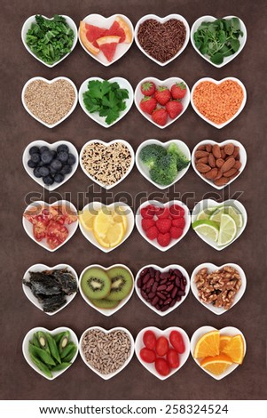 Large selection of diet detox super food in heart shaped porcelain bowls. - stock photo