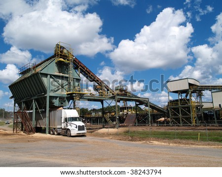 Large semi truck being filled with pine bark beside a lumber yard. - stock photo