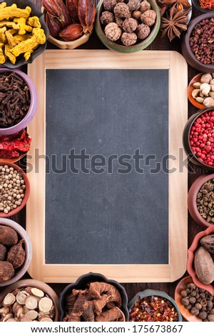 Large set of spices and seasonings with chalk board, top view