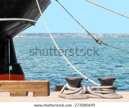 Large ship docked with rusty boat anchor chain and shackle with thick rope tied to heavy steel docking cleats. Blue ocean and sky background.  - stock photo