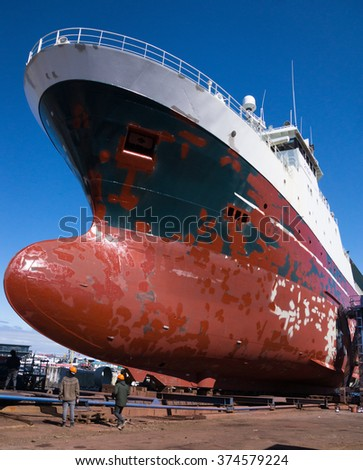 Large ship in dry dock for repairs and painting - stock photo