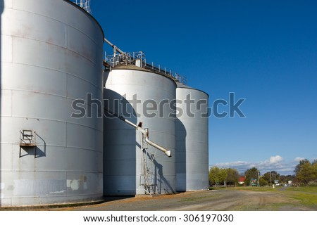 Large silos on a clear day, with drop pipe showing. - stock photo