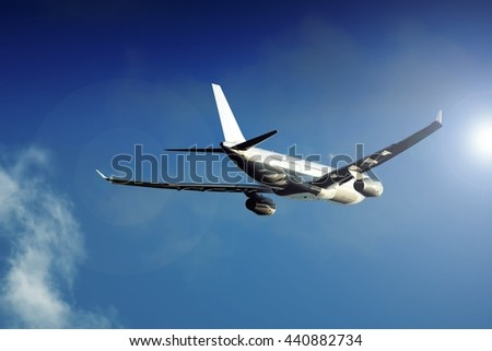 large size heavy intercontinental wide body twin jet engine passenger jet aircraft flying towards the low sun - stock photo