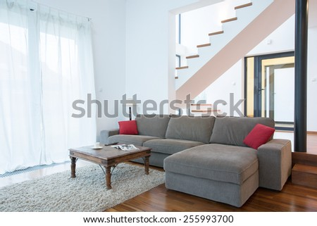 Large sofa in spacious living room in modern house - stock photo