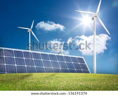 Large solar panel and three wind turbines in a sunny field