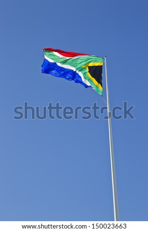 Large South African flag flapping in the wind with the sun shining from behind