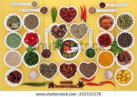 Large spice and herb collection in measuring spoons, mortar with pestle, porcelain dishes and loose over wooden yellow background. - stock photo