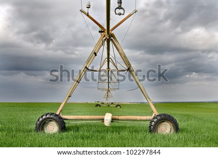 large sprinkler that is used to irrigate the field - stock photo