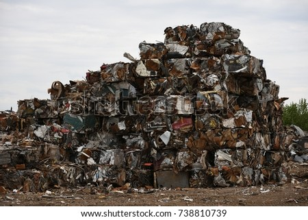 Large stack of compacted scrap iron metal blocks for scrap metal recycling.