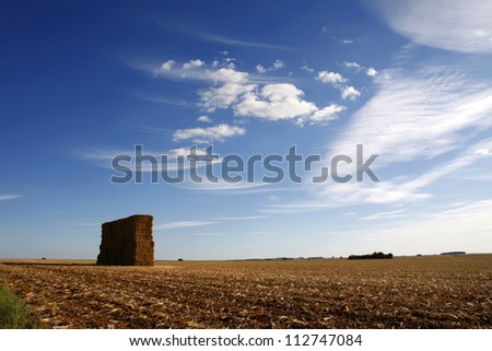 Large stack of hay bales against a blue sky