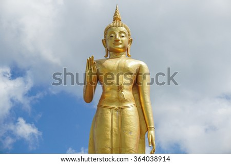 large statue of Lord Buddha,blue sky and clouds background This is traditional and generic style in thailand.No any trademark or restrict matter in this photo. - stock photo