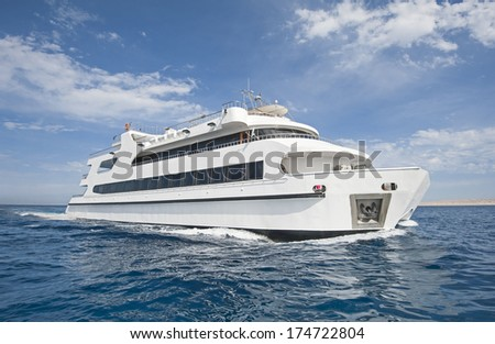 Large steel luxury private catamaran motor yacht sailing out at sea