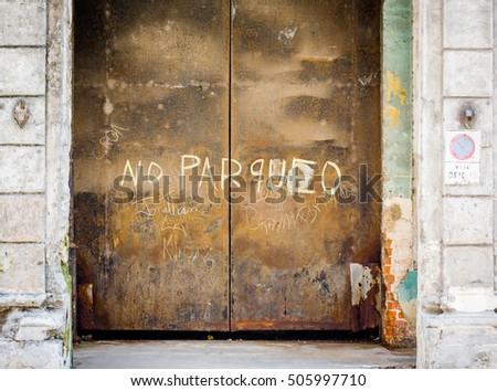 Large steel rusty doors in Havana, Cuba with no parqueo sign