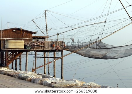 large stilt house by the sea and fishing nets of fishermen - stock photo