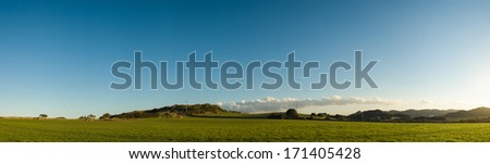 Large stitched panorama of a beautiful sunset landscape of lush green farmland painted with subtle evening shades. - stock photo