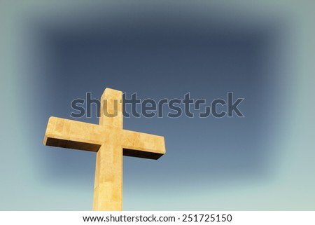 Large stone cross against a blue and white background - stock photo