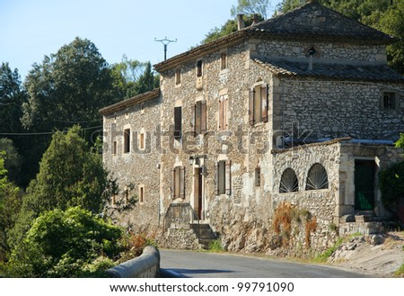 Large stone house in summer sun with trees