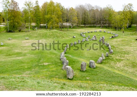 Large stone ship made of raised stones in Anundshog, Sweden. Also seen are burial mounds in the field.