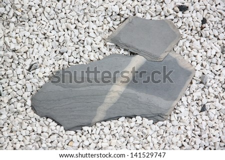 Large stone slabs on white small rock.