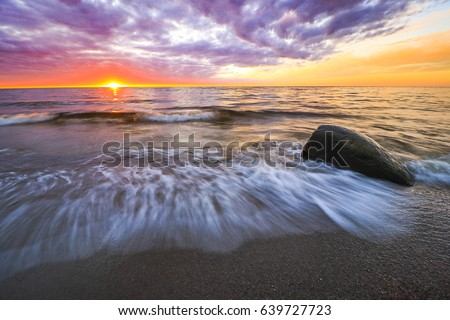 large stones in the sea at sunset