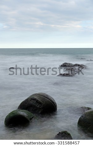 Large stones in the sea foam. Calm sea long exposure shot