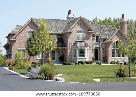 Large suburban brick and stone home with arched entry - stock photo