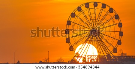 large sun at sunset, ferris wheel